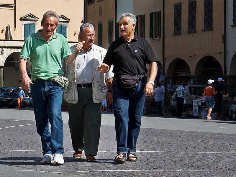 tre cittadini di Figline Valdarno attraversano piazza Marsilio Ficino