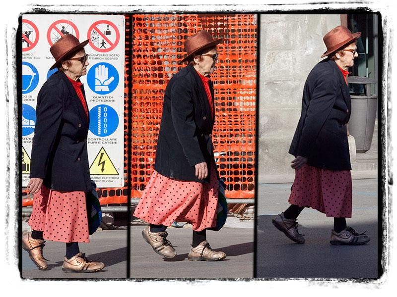 Una signora assai in gamba procede a passo svelto attraverso la piazza Ficino