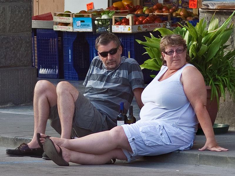 Una coppia di turisti costretti a sedersi per terra a causa della totale mancanza di panchine in piazza