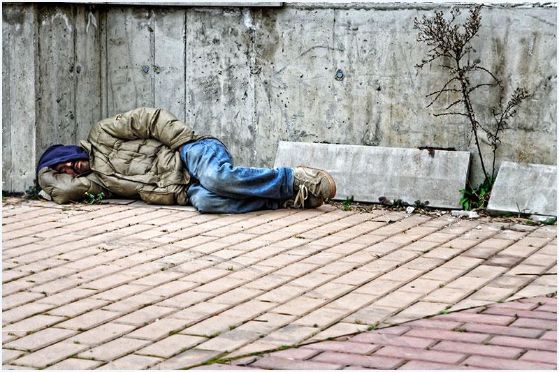 un migrante dorme nel mezzo di spazzatura, riparandosi con un muro di cemento