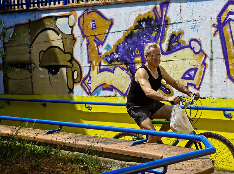 Un anziano percorre in bicicletta il sottopasso della ferrovia