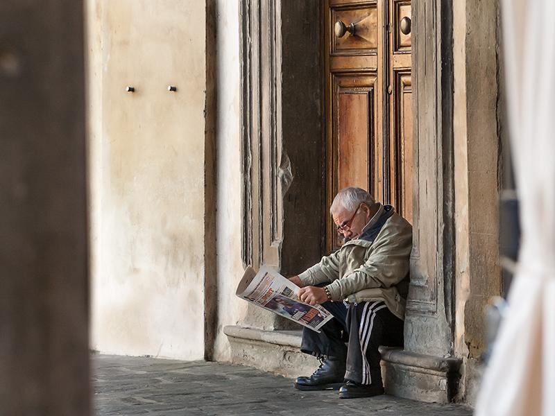 un cittadino anziano seduto sui gradini della Collegiata a Figline Valdarno