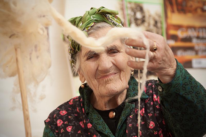 Una signora anziana fila la lana